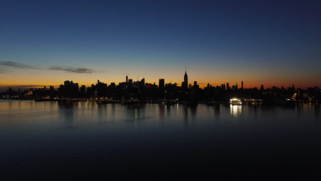 Wide shot over Hudson River of New York City skyline silhouetted against orange sunrise