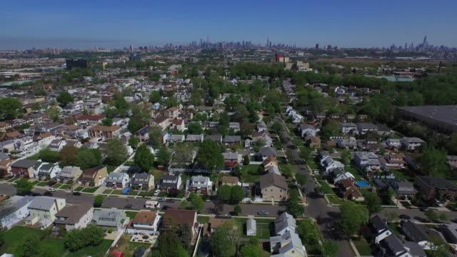 Wide shot over New Jersey suburb, moving toward New York City skyline on horizon