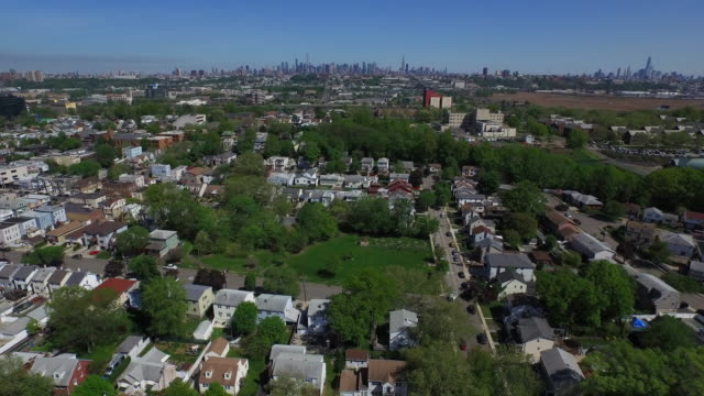 Wide shot over New Jersey suburb, pulling away from New York City skyline on horizon