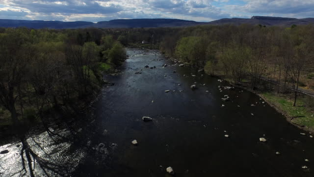 wide shot over rocky river at center of frame, with tree lined banks  - new paltz ny stock videos and b-roll footage
