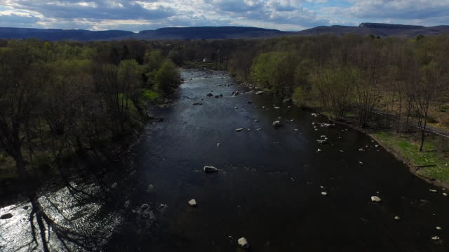 wide shot over rocky river at center of frame, with tree lined banks  - new paltz stock videos and b-roll footage
