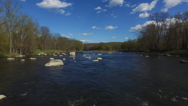 wide shot over rocky river lined by trees with a bright blue, cloudy sky in upstate new york - contea di ulster stato di new york video stock e b–roll