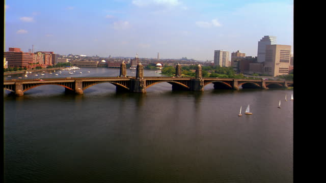 aerial pow wide shot over sailboats toward longfellow bridge with traffic + overhead bridge / boston, ma - チャールズ川点の映像素材/bロール