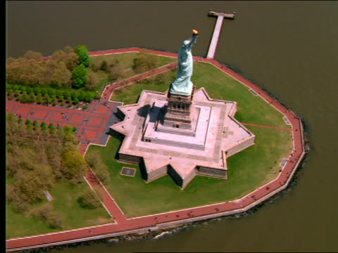 aerial wide shot over statue of liberty + liberty island / nyc - weibliche figur stock-videos und b-roll-filmmaterial