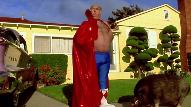 Wide shot overweight mature man wearing superhero cape and tights running into front yard / boar in foreground