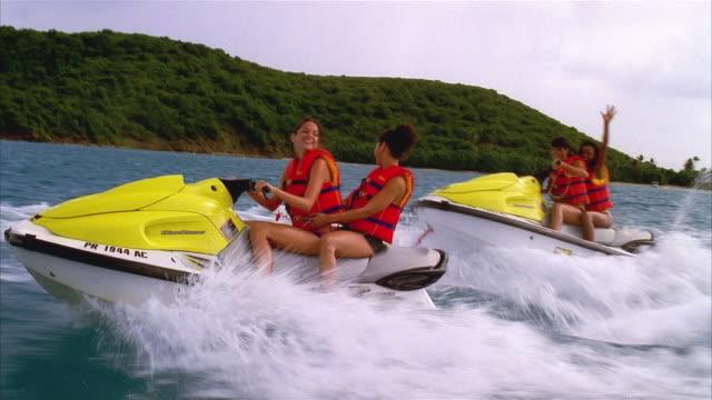 wide shot pairs of women jet skiing off the coast of palomino island / san juan, puerto rico - acquascooter video stock e b–roll