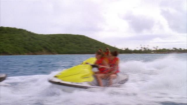 Wide shot pairs of women jet skiing off the coast of Palomino Island / San Juan, Puerto Rico