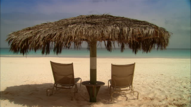 wide shot palapa shading lounge chairs on beach near surf/ harbor island, bahamas - outdoor chair stock videos and b-roll footage