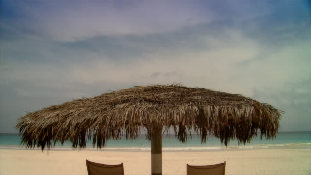 stockvideo's en b-roll-footage met wide shot palapa shading lounge chairs on beach near surf/ harbor island, bahamas - bahama's