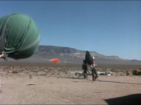 1962 wide shot pan 2 men releasing weather balloon in desert / nevada / audio - meteorology stock videos & royalty-free footage