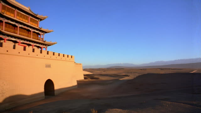 vidéos et rushes de wide shot pan across desert landscape to pagodas of fort jiayuguan / china - grande muraille de chine