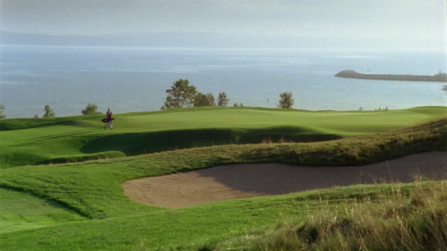 Wide shot pan across sand trap on golf course / men walking on green / water in background / Bay Harbor, Michigan