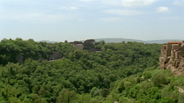 Wide shot pan across treetops to hillside town of Pitigliano / Tuscany, Italy