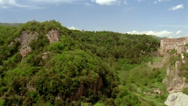 Wide shot pan across treetops to hillside town of Sorano, Tuscany, Italy