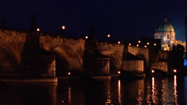wide shot pan along charles bridge on vltava river at night / prague, czech republic - river vltava stock videos & royalty-free footage