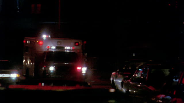 wide shot pan ambulance with flashing lights passing other cars on street at night / new york city - ambulance stock videos & royalty-free footage
