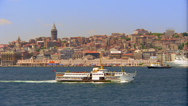 wide shot pan boat moving through harbor with istanbul in background / turkey - 1995 stock videos & royalty-free footage
