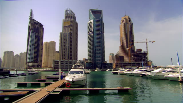 Wide shot pan boats in marina surrounded by skyscrapers/ Dubai