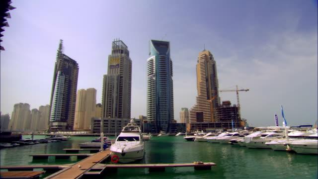 wide shot pan boats in marina surrounded by skyscrapers/ dubai - 2007年点の映像素材/bロール