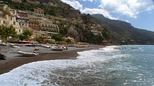 Wide shot pan boats sitting on beach at the foot of hill town of Positano / Amalfi Coast, Campania, Italy