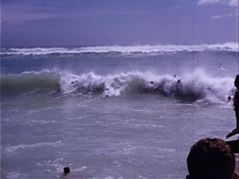 1953 Wide shot pan Body surfers riding waves in Pacific Ocean on Waikiki Beach / Honolulu, Hawaii, USA
