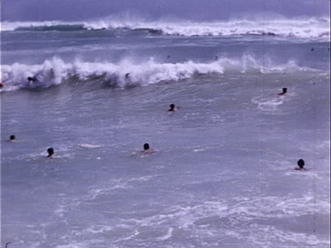 1953 wide shot pan body surfers riding waves in pacific ocean on waikiki beach / honolulu, hawaii, usa  - unknown gender stock videos & royalty-free footage