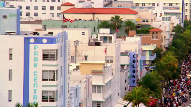 Wide shot pan buildings and crowds walking in streets in Miami Beach / Florida
