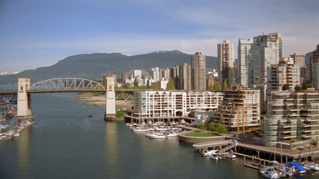 vídeos y material grabado en eventos de stock de wide shot pan burrard street bridge over false creek to buildings on waterfront / vancouver - kelly mason videos