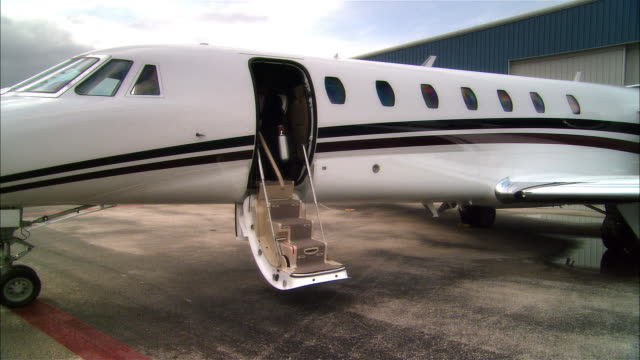 wide shot pan businessman exiting private jet and waving at opa locka airport/ miami, florida, usa - millionär stock-videos und b-roll-filmmaterial