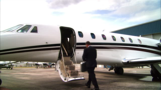 wide shot pan businessman walking toward and entering private jet and waving at opa locka airport/ miami, florida, usa - 書類鞄点の映像素材/bロール