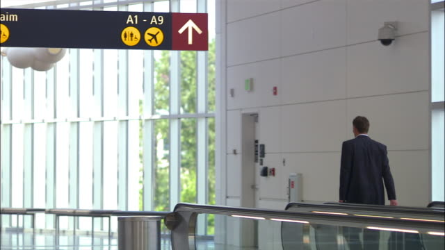 wide shot pan businessman with luggage getting off of moving sidewalk at airport/ seattle - simbolo informazioni video stock e b–roll