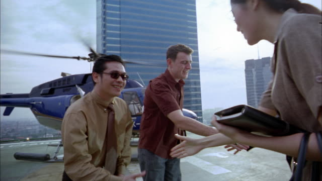 wide shot pan businesspeople shaking hands on building rooftop w/helicopter in background - inchinarsi video stock e b–roll