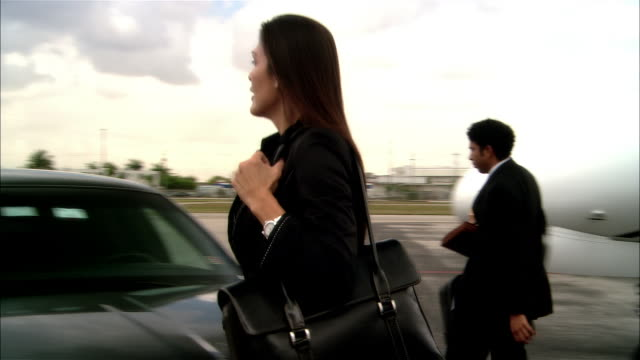 vídeos de stock e filmes b-roll de wide shot pan businesswoman and businessman exiting private jet and entering chauffeur-driven luxury car at opa locka airport/ miami, florida, usa - hangar