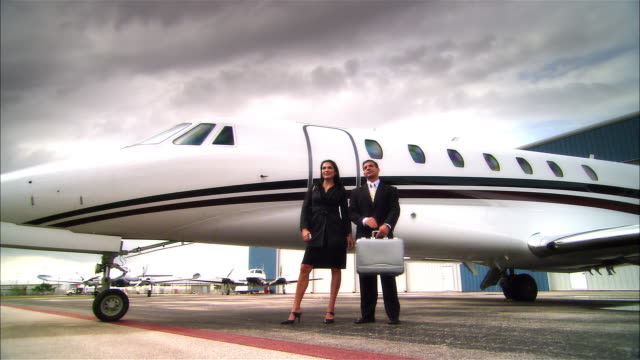 Wide shot pan Businesswoman and businessman standing near private jet at Opa Locka Airport/ Miami, Florida, USA