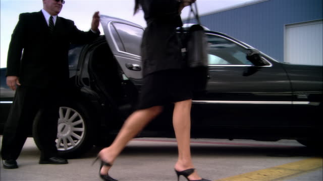 wide shot pan businesswoman exiting chauffeur-driven luxury car and greeted by pilot at door of private jet at opa locka airport/ miami, florida, usa - private jet stock videos & royalty-free footage