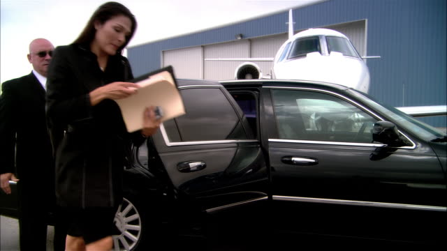 wide shot pan businesswoman exiting chauffeur-driven luxury car and greeted by pilot at door of private jet at opa locka airport/ miami, florida, usa - chauffeur stock videos and b-roll footage