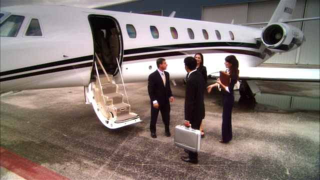 Wide shot pan Businesswoman kissing female colleague and businessmen shaking hands then entering private jet at Opa Locka Airport/ Miami, Florida, USA