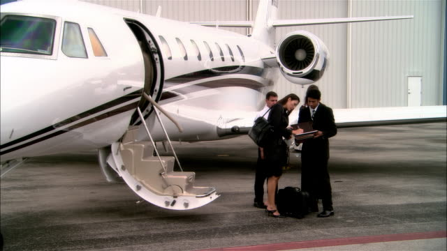 stockvideo's en b-roll-footage met wide shot pan businesswoman signing documents for colleagues and entering private jet near chauffeur-driven luxury car at opa locka airport/ miami, florida, usa - overhemd en stropdas
