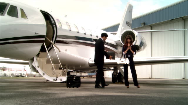 wide shot pan businesswoman text messaging while businessman shows her a file near private jet at opa locka airport/ miami, florida, usa - accessibility stock videos & royalty-free footage