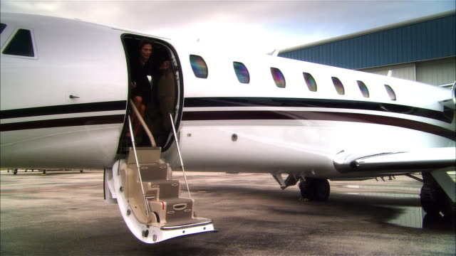 wide shot pan businesswoman waving and exiting private jet then greeting businessman at opa locka airport/ miami, florida, usa - 降り立つ点の映像素材/bロール