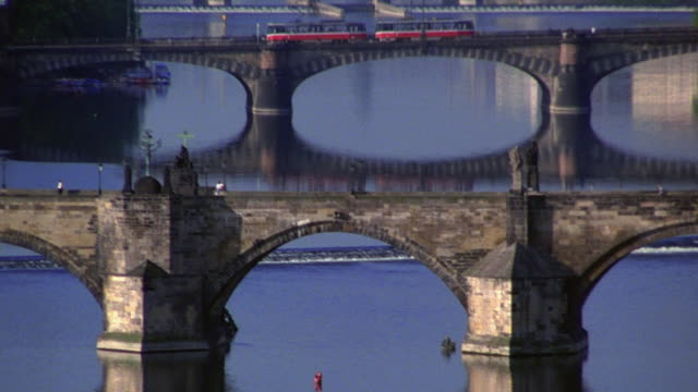 wide shot pan charles bridge with train crossing other bridge in background on vltava river / prague, czech republic - vltava river stock videos & royalty-free footage