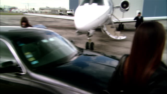 wide shot pan chauffeur opening luxury car door for businesswomen who greet colleague then enter private jet at opa locka airport/ miami, florida, usa - chauffeur stock videos and b-roll footage