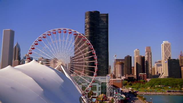 Wide shot pan Chicago skyline / ferris wheel and Chicago River in foreground