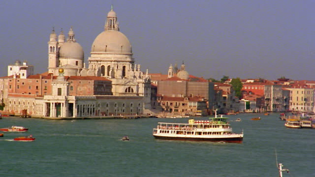 Wide shot pan Chiesa della Salute and boats on water in Venice / Italy