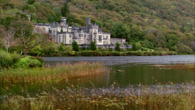 wide shot pan church on lake / ireland - 2002 stock videos & royalty-free footage