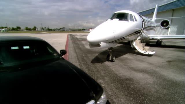 Wide shot pan - close-up Black car parking on runway near private jet outside hangar at Opa Locka Airport/ Miami, Florida, USA