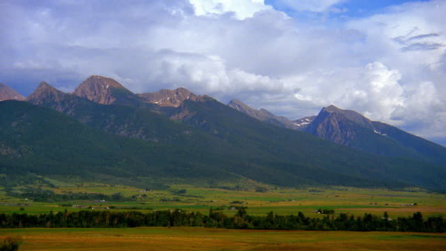 Wide shot pan clouds over mountain range with plain in foreground / Montana