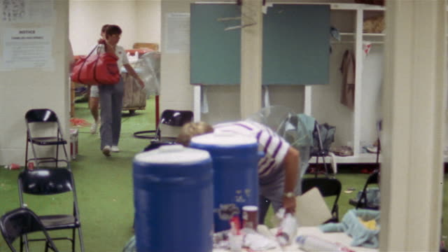 1985 wide shot pan coach steve spurrier drinking from water cooler and leaving locker room before game / usa  - water cooler stock videos & royalty-free footage