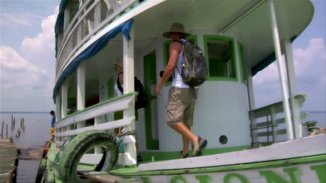 vidéos et rushes de wide shot pan couple walking from bow of ferry boat to side as it sits at dock in rio negro/ the amazon, brazil - couple d'âge moyen
