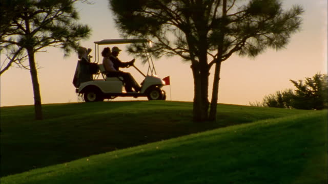 wide shot pan couples driving golf carts across horizon on golf course at sunset - golf cart stock videos & royalty-free footage